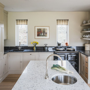 Design ideas for a classic u-shaped kitchen/diner in Oxfordshire with a submerged sink, shaker cabinets, beige cabinets, integrated appliances, medium hardwood flooring, an island and brown floors.