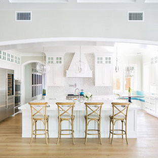 Transitional eat-in kitchen inspiration - Example of a transitional light wood floor and beige floor eat-in kitchen design in Orange County with a farmhouse sink, shaker cabinets, white cabinets, gray backsplash, stainless steel appliances, an island and white countertops