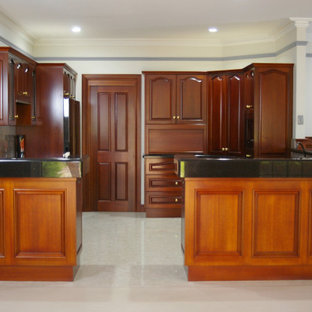 Design ideas for a large traditional u-shaped open plan kitchen in Adelaide with a double-bowl sink, raised-panel cabinets, dark wood cabinets, granite benchtops, multi-coloured splashback, stone slab splashback, white appliances, marble floors, no island and multi-coloured floor.
