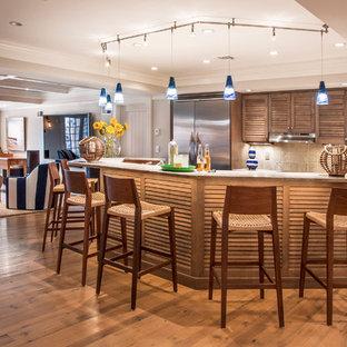 Ispirazione per una piccola cucina classica con ante a persiana, ante in legno scuro, top in superficie solida, paraspruzzi beige, paraspruzzi con piastrelle in ceramica, elettrodomestici in acciaio inossidabile, pavimento in legno massello medio e penisola
