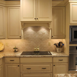 This is an example of a large traditional l-shaped eat-in kitchen in Other with an undermount sink, white cabinets, granite benchtops, black splashback, stone tile splashback, stainless steel appliances, travertine floors and with island.