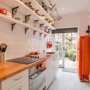 На фото: маленькая отдельная, параллельная кухня в стиле фьюжн с накладной раковиной, плоскими фасадами, белыми фасадами, деревянной столешницей, белым фартуком, фартуком из плитки кабанчик, цветной техникой и деревянным полом без острова с