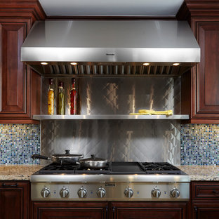 Inspiration for a mid-sized traditional u-shaped eat-in kitchen in Los Angeles with a triple-bowl sink, raised-panel cabinets, dark wood cabinets, quartz benchtops, multi-coloured splashback, glass tile splashback, stainless steel appliances, marble floors, a peninsula and beige floor.