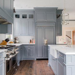 Klassische Küche in L-Form mit Landhausspüle, profilierten Schrankfronten, grauen Schränken, Küchenrückwand in Weiß, Rückwand aus Mosaikfliesen, Elektrogeräten mit Frontblende, Kücheninsel und braunem Boden in Cleveland