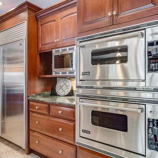 Geräumige Klassische Wohnküche in L-Form mit Einbauwaschbecken, profilierten Schrankfronten, hellbraunen Holzschränken, Granit-Arbeitsplatte, Küchenrückwand in Rot, Rückwand aus Backstein, Küchengeräten aus Edelstahl, Keramikboden, Kücheninsel, beigem Boden und schwarzer Arbeitsplatte in Chicago