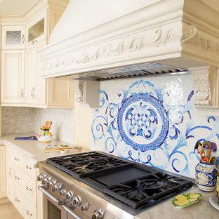 Große Mediterrane Wohnküche in L-Form mit Unterbauwaschbecken, profilierten Schrankfronten, beigen Schränken, Granit-Arbeitsplatte, Küchenrückwand in Grau, Rückwand aus Stäbchenfliesen, Küchengeräten aus Edelstahl, Porzellan-Bodenfliesen und Kücheninsel in Los Angeles