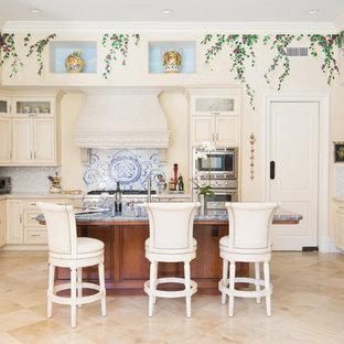ロサンゼルスの大きい地中海スタイルのおしゃれなキッチン (アンダーカウンターシンク、レイズドパネル扉のキャビネット、ベージュのキャビネット、御影石カウンター、グレーのキッチンパネル、ボーダータイルのキッチンパネル、シルバーの調理設備の、磁器タイルの床) の写真