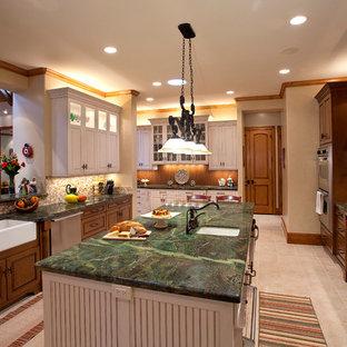 Exemple d'une grande cuisine américaine parallèle chic avec un évier de ferme, un placard avec porte à panneau surélevé, un plan de travail en granite, un électroménager en acier inoxydable, des portes de placard marrons, une crédence beige, un îlot central, un sol beige et un plan de travail vert.