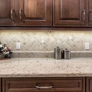 Esempio di una cucina chic di medie dimensioni con lavello sottopiano, ante con bugna sagomata, ante marroni, top in quarzo composito, paraspruzzi beige, paraspruzzi con piastrelle in pietra e pavimento in gres porcellanato