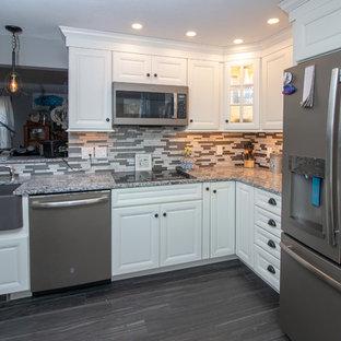 マンチェスターの中サイズのトラディショナルスタイルのおしゃれなキッチン (エプロンフロントシンク、フラットパネル扉のキャビネット、白いキャビネット、御影石カウンター、グレーのキッチンパネル、ガラス板のキッチンパネル、シルバーの調理設備の、クッションフロア、アイランドなし、グレーの床、マルチカラーのキッチンカウンター) の写真
