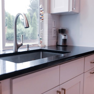 Inspiration for a mid-sized traditional u-shaped eat-in kitchen in Seattle with shaker cabinets, granite benchtops, white splashback, ceramic splashback, stainless steel appliances, light hardwood floors, black benchtop, an integrated sink, white cabinets and with island.