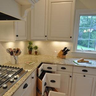 ボストンの中くらいのトラディショナルスタイルのおしゃれなキッチン (アンダーカウンターシンク、レイズドパネル扉のキャビネット、白いキャビネット、御影石カウンター、ベージュキッチンパネル、サブウェイタイルのキッチンパネル、シルバーの調理設備、無垢フローリング) の写真