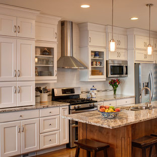 Elegant galley kitchen photo in Salt Lake City with a double-bowl sink, shaker cabinets, white cabinets, white backsplash, subway tile backsplash and stainless steel appliances