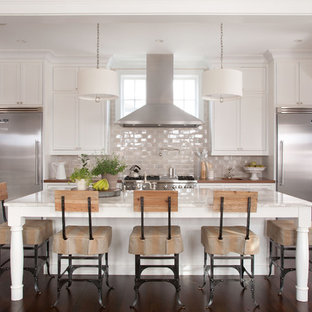 Design ideas for a traditional galley kitchen in Denver with stainless steel appliances, marble benchtops, recessed-panel cabinets, white cabinets and glass tile splashback.