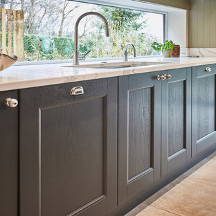 Inspiration for a mid-sized traditional single-wall open plan kitchen in Other with a drop-in sink, shaker cabinets, green cabinets, quartzite benchtops, white splashback, window splashback, stainless steel appliances, porcelain floors, with island, beige floor and white benchtop.