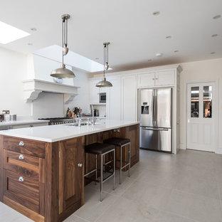 Ejemplo de cocina clásica con fregadero de doble seno, armarios estilo shaker, puertas de armario blancas, electrodomésticos de acero inoxidable y una isla