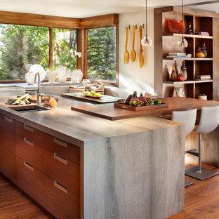 デンバーのコンテンポラリースタイルのおしゃれなアイランドキッチン (エプロンフロントシンク、フラットパネル扉のキャビネット、中間色木目調キャビネット、ガラスまたは窓のキッチンパネル、無垢フローリング、茶色い床、グレーのキッチンカウンター) の写真