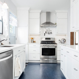 This is an example of a mid-sized transitional galley separate kitchen in Seattle with an undermount sink, shaker cabinets, white cabinets, quartz benchtops, white splashback, subway tile splashback, stainless steel appliances, linoleum floors, no island, blue floor and white benchtop.