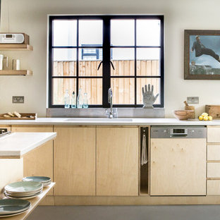 Photo of a scandinavian kitchen in Oxfordshire with a single-bowl sink, flat-panel cabinets, light wood cabinets, window splashback, integrated appliances, an island, grey floors and white worktops.