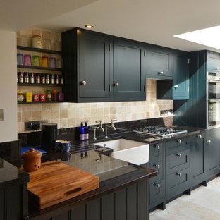 Mittelgroße Landhausstil Wohnküche ohne Insel in L-Form mit Landhausspüle, Schrankfronten im Shaker-Stil, blauen Schränken, Granit-Arbeitsplatte, Küchenrückwand in Beige, Küchengeräten aus Edelstahl, Kalkstein und Kalk-Rückwand in Kent