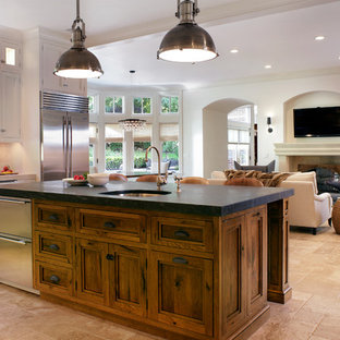 Large traditional l-shaped kitchen/diner in New York with a submerged sink, recessed-panel cabinets, medium wood cabinets, beige splashback, stainless steel appliances, soapstone worktops and travertine flooring.