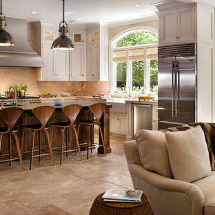Photo of a large transitional l-shaped eat-in kitchen in New York with a farmhouse sink, recessed-panel cabinets, white cabinets, beige splashback, stainless steel appliances, soapstone benchtops, travertine floors, beige floor and travertine splashback.