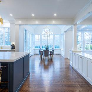 Diseño de cocina clásica renovada, grande, abierta, con fregadero bajoencimera, armarios estilo shaker, puertas de armario blancas, encimera de cuarzo compacto, salpicadero blanco, electrodomésticos de acero inoxidable, suelo de madera oscura, una isla, suelo marrón y encimeras blancas