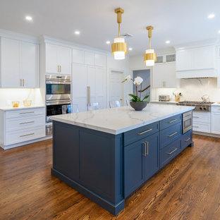 フィラデルフィアの広いトランジショナルスタイルのおしゃれなアイランドキッチン (アンダーカウンターシンク、シェーカースタイル扉のキャビネット、白いキャビネット、クオーツストーンカウンター、白いキッチンパネル、クオーツストーンのキッチンパネル、シルバーの調理設備、濃色無垢フローリング、茶色い床、白いキッチンカウンター) の写真