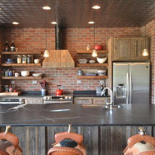 他の地域の広いラスティックスタイルのおしゃれなキッチン (オープンシェルフ、中間色木目調キャビネット、ソープストーンカウンター、クッションフロア、エプロンフロントシンク、赤いキッチンパネル、レンガのキッチンパネル、シルバーの調理設備、茶色い床) の写真
