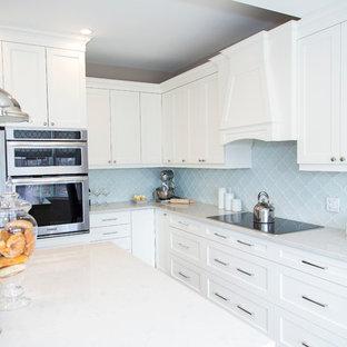 トロントの大きいシャビーシック調のおしゃれなキッチン (ダブルシンク、シェーカースタイル扉のキャビネット、白いキャビネット、大理石カウンター、青いキッチンパネル、ガラスタイルのキッチンパネル、シルバーの調理設備の、濃色無垢フローリング) の写真