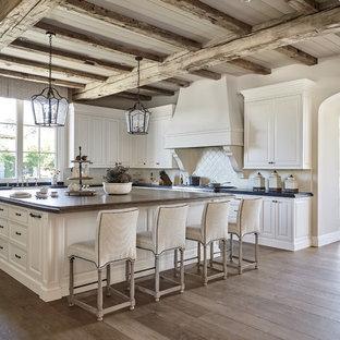 フェニックスの広いトランジショナルスタイルのおしゃれなキッチン (レイズドパネル扉のキャビネット、ベージュキッチンパネル、白いキャビネット、エプロンフロントシンク、ソープストーンカウンター、セラミックタイルのキッチンパネル、無垢フローリング、茶色い床) の写真