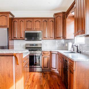 Offene, Mittelgroße Rustikale Küche in L-Form mit Unterbauwaschbecken, profilierten Schrankfronten, hellbraunen Holzschränken, Granit-Arbeitsplatte, Küchenrückwand in Weiß, Rückwand aus Metrofliesen, Küchengeräten aus Edelstahl, braunem Holzboden, Kücheninsel, braunem Boden und grauer Arbeitsplatte in Sonstige