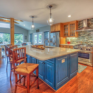 シャーロットの広いトランジショナルスタイルのおしゃれなキッチン (アンダーカウンターシンク、シェーカースタイル扉のキャビネット、中間色木目調キャビネット、コンクリートカウンター、マルチカラーのキッチンパネル、石タイルのキッチンパネル、シルバーの調理設備、無垢フローリング、青い床) の写真