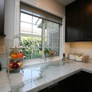 Mittelgroße Klassische Küche ohne Insel in L-Form mit Doppelwaschbecken, Schrankfronten mit vertiefter Füllung, dunklen Holzschränken, Quarzit-Arbeitsplatte, Küchenrückwand in Weiß, Rückwand aus Glasfliesen, Küchengeräten aus Edelstahl und Porzellan-Bodenfliesen in Orange County