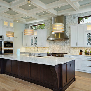Idéer för medelhavsstil l-kök, med luckor med infälld panel, vita skåp, flerfärgad stänkskydd, rostfria vitvaror, ljust trägolv, en köksö och stänkskydd i mosaik