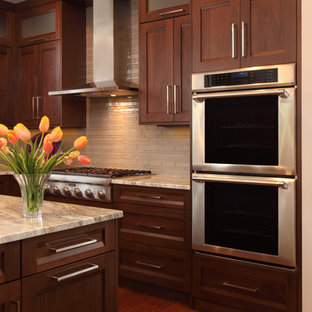 Example of a large transitional u-shaped dark wood floor and brown floor enclosed kitchen design in Minneapolis with an undermount sink, shaker cabinets, dark wood cabinets, marble countertops, beige backsplash, porcelain backsplash, stainless steel appliances and an island