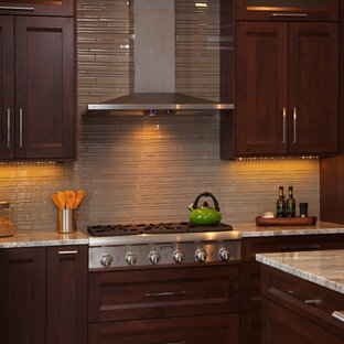 Large transitional u-shaped dark wood floor and brown floor enclosed kitchen photo in Minneapolis with an undermount sink, shaker cabinets, dark wood cabinets, marble countertops, beige backsplash, porcelain backsplash, stainless steel appliances and an island