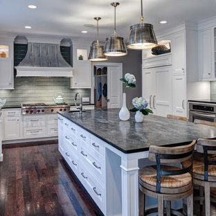Design ideas for a transitional u-shaped eat-in kitchen in Chicago with a farmhouse sink, white cabinets, soapstone benchtops, green splashback, glass tile splashback, recessed-panel cabinets and panelled appliances.