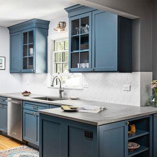 デトロイトの小さいビーチスタイルのおしゃれなキッチン (アンダーカウンターシンク、シェーカースタイル扉のキャビネット、青いキャビネット、クオーツストーンカウンター、グレーのキッチンパネル、磁器タイルのキッチンパネル、シルバーの調理設備の、淡色無垢フローリング、アイランドなし、茶色い床、グレーのキッチンカウンター) の写真