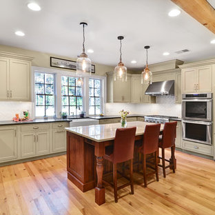 Large farmhouse kitchen designs - Large cottage u-shaped brown floor and light wood floor kitchen photo in Baltimore with a farmhouse sink, shaker cabinets, beige cabinets, white backsplash, an island, soapstone countertops, glass tile backsplash and paneled appliances