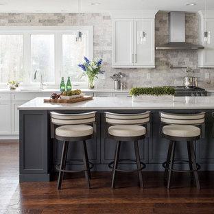 Неиссякаемый источник вдохновения для домашнего уюта: большая угловая кухня в стиле современная классика с белыми фасадами, столешницей из кварцевого агломерата, серым фартуком, техникой из нержавеющей стали, темным паркетным полом, островом, врезной раковиной, фасадами в стиле шейкер, коричневым полом, фартуком из каменной плитки и обеденным столом