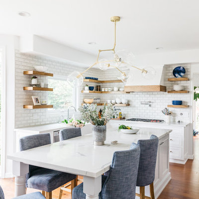 Inspiration for a mid-sized transitional u-shaped medium tone wood floor and brown floor eat-in kitchen remodel in Los Angeles with a farmhouse sink, recessed-panel cabinets, white cabinets, quartzite countertops, white backsplash, subway tile backsplash, stainless steel appliances, an island and white countertops
