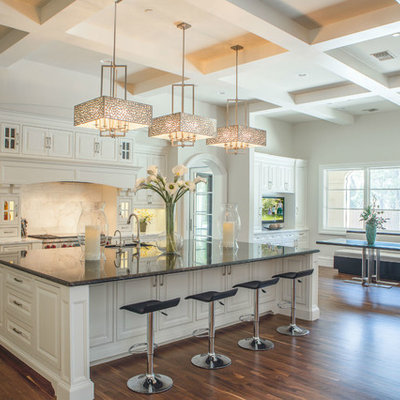 Inspiration for a huge transitional medium tone wood floor eat-in kitchen remodel in Dallas with an undermount sink, raised-panel cabinets, white cabinets, marble countertops, white backsplash, stainless steel appliances and an island