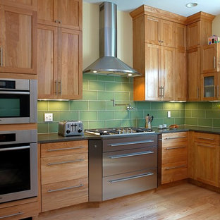 Transitional kitchen in Boston with glass tile splashback, stainless steel appliances, green splashback and medium wood cabinets.