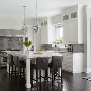 Ejemplo de cocina comedor clásica renovada con armarios con paneles empotrados, puertas de armario blancas, salpicadero verde, electrodomésticos de acero inoxidable, suelo de madera oscura y una isla