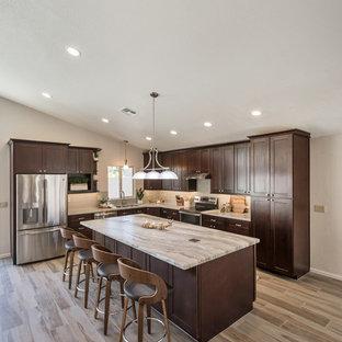 Idéer för att renovera ett mellanstort vintage flerfärgad flerfärgat kök, med en undermonterad diskho, skåp i shakerstil, bruna skåp, granitbänkskiva, grått stänkskydd, stänkskydd i glaskakel, rostfria vitvaror, klinkergolv i porslin, en köksö och brunt golv