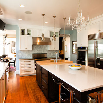 Example of a mid-sized classic u-shaped medium tone wood floor eat-in kitchen design in Chicago with recessed-panel cabinets, a double-bowl sink, white cabinets, quartz countertops, stainless steel appliances, gray backsplash and an island