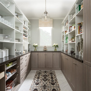 Bild på ett stort vintage kök, med bruna skåp, marmorbänkskiva, blått stänkskydd, rostfria vitvaror och klinkergolv i keramik