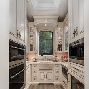 Inspiration for an expansive traditional u-shaped separate kitchen in Phoenix with a farmhouse sink, raised-panel cabinets, light wood cabinets, quartzite benchtops, beige splashback, porcelain splashback, stainless steel appliances, medium hardwood floors, no island, brown floor and beige benchtop.