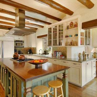 アルバカーキの中くらいのトラディショナルスタイルのおしゃれなキッチン (シェーカースタイル扉のキャビネット、ヴィンテージ仕上げキャビネット、ベージュキッチンパネル、パネルと同色の調理設備、濃色無垢フローリング) の写真